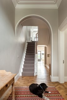 Outside of the extension, the Victorian house's interior appears largely unchanged. However, NOJI Architecture added a long window to the hallway that connects the extension with the entrance. Light from the extension flows into the rest of the ground floor and connects the new space to its environs.