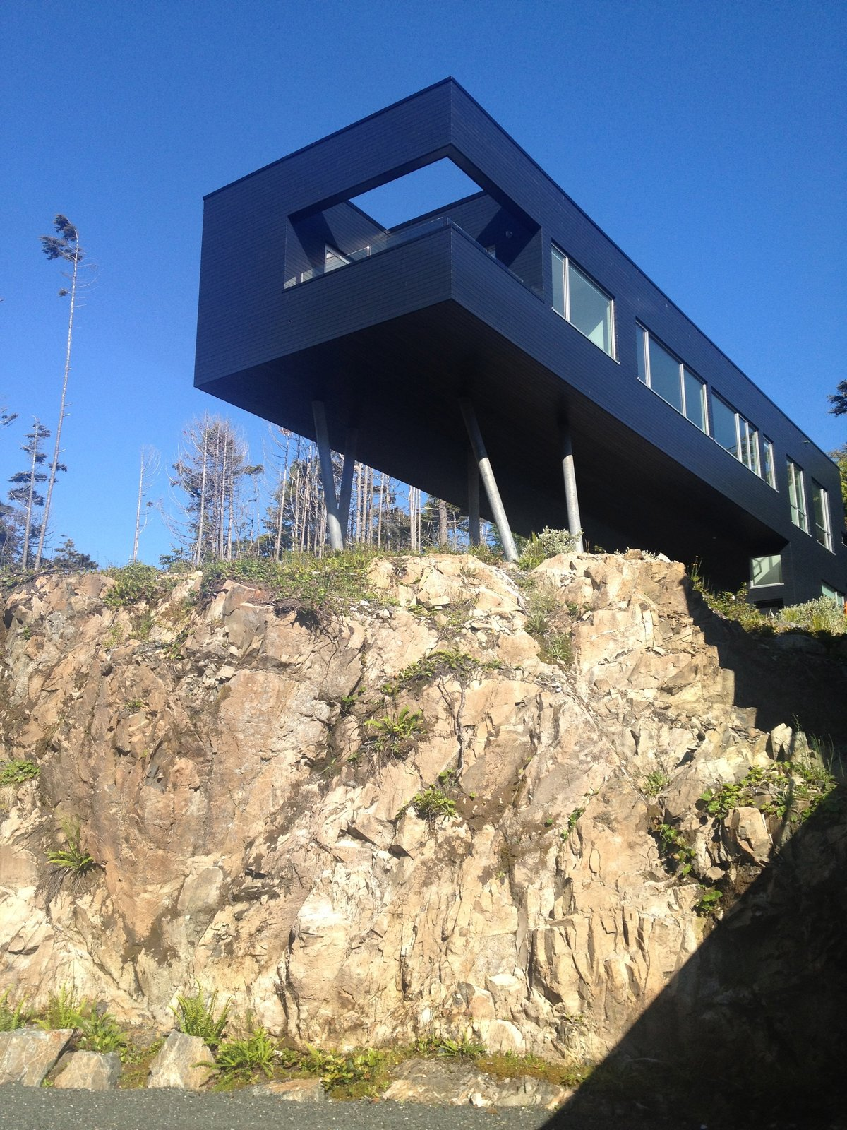 Exterior, Prefab Building Type, and Flat RoofLine The L-shaped secondary building perches over a craggy escarpment. It offers the best vantage point for taking in the moss-planted roof, forest, and ocean.  Best Photos from A Giant, 20-Module Prefab Perched Across a Coastal Site in British Columbia