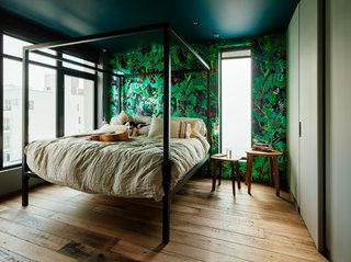 Zames decided on Farrow & Ball's Hague Blue color for the bedroom ceiling to make the space feel more intimate, but juxtaposed it with another wallpaper from Flavor Paper. The bed is from Room & Board and the Fawn tables are by Rich Brilliant Willing.