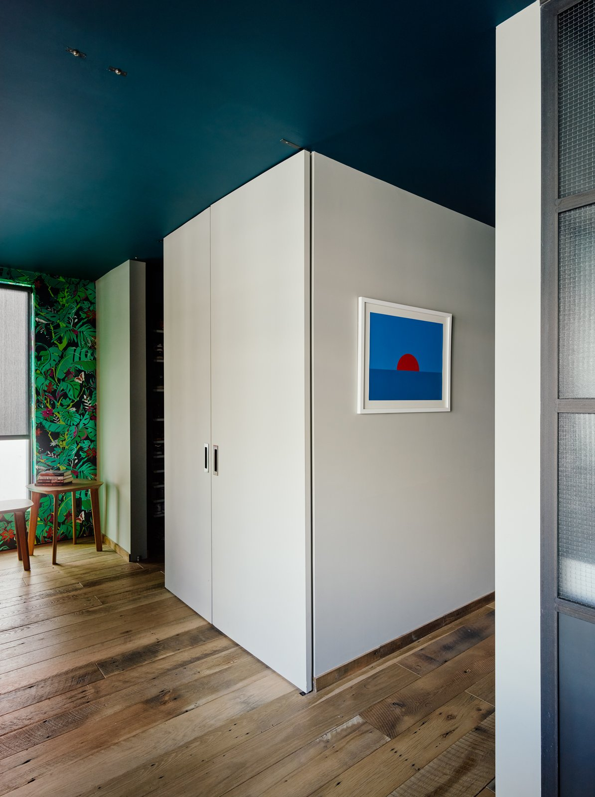 A system of full-height panel doors rotate in the space, closing off the bedroom and walk-in closet from the home office—a key feature for the residents, who often work from home.  Photo 8 of 9 in Two Apartments Were Combined into This Inviting Brooklyn Home