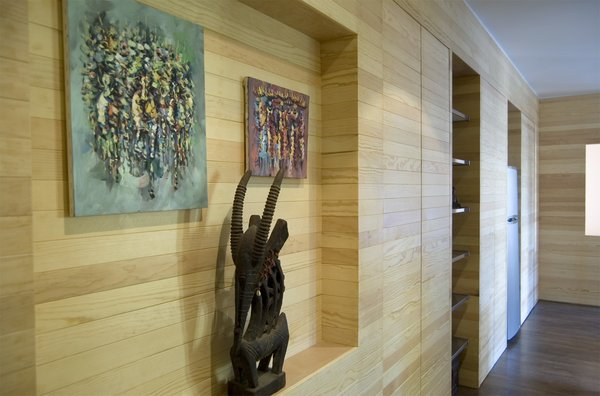 The slatted wood wall runs the entire length of the 450-square-foot studio, beginning in the entryway, where it displays two African paintings and a sculpture. Further along, the wall opens to accommodate a refrigerator and clothes storage.