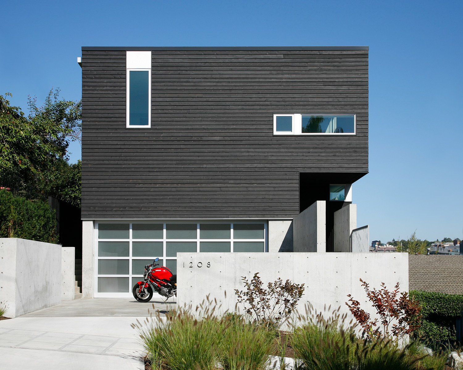 """""""The house turns its back to the street while opening up to the views to the northeast through a large glazed corner window system,"""" Hutchison says. One-by-four and one-by-six inch cedar siding, which were pre-stained in Cabot Semi-Transparent Black, were placed vertically and horizontally on the exterior as a subtle detail.  Search """"cedar"""" from Portage Bay Bungalow"""