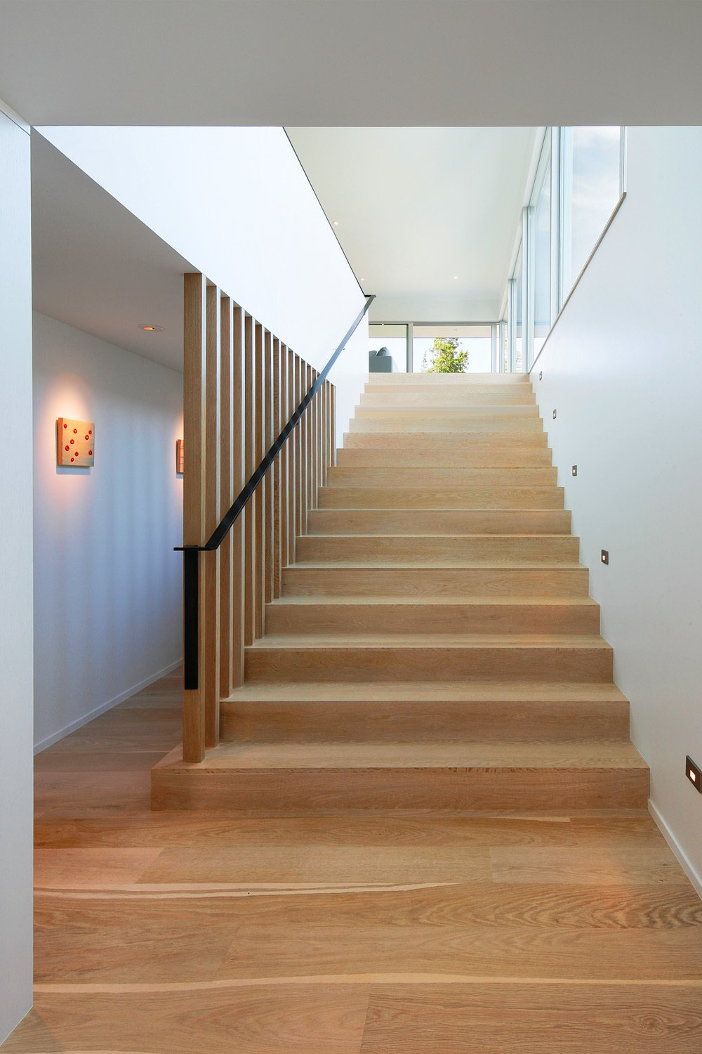 Custom bleached-white oak flooring covers the floors, including on the staircase to the property's second floor. Juno five-inch LED recessed wall lighting illuminates the steps at night.  Portage Bay Bungalow by Kelly Dawson