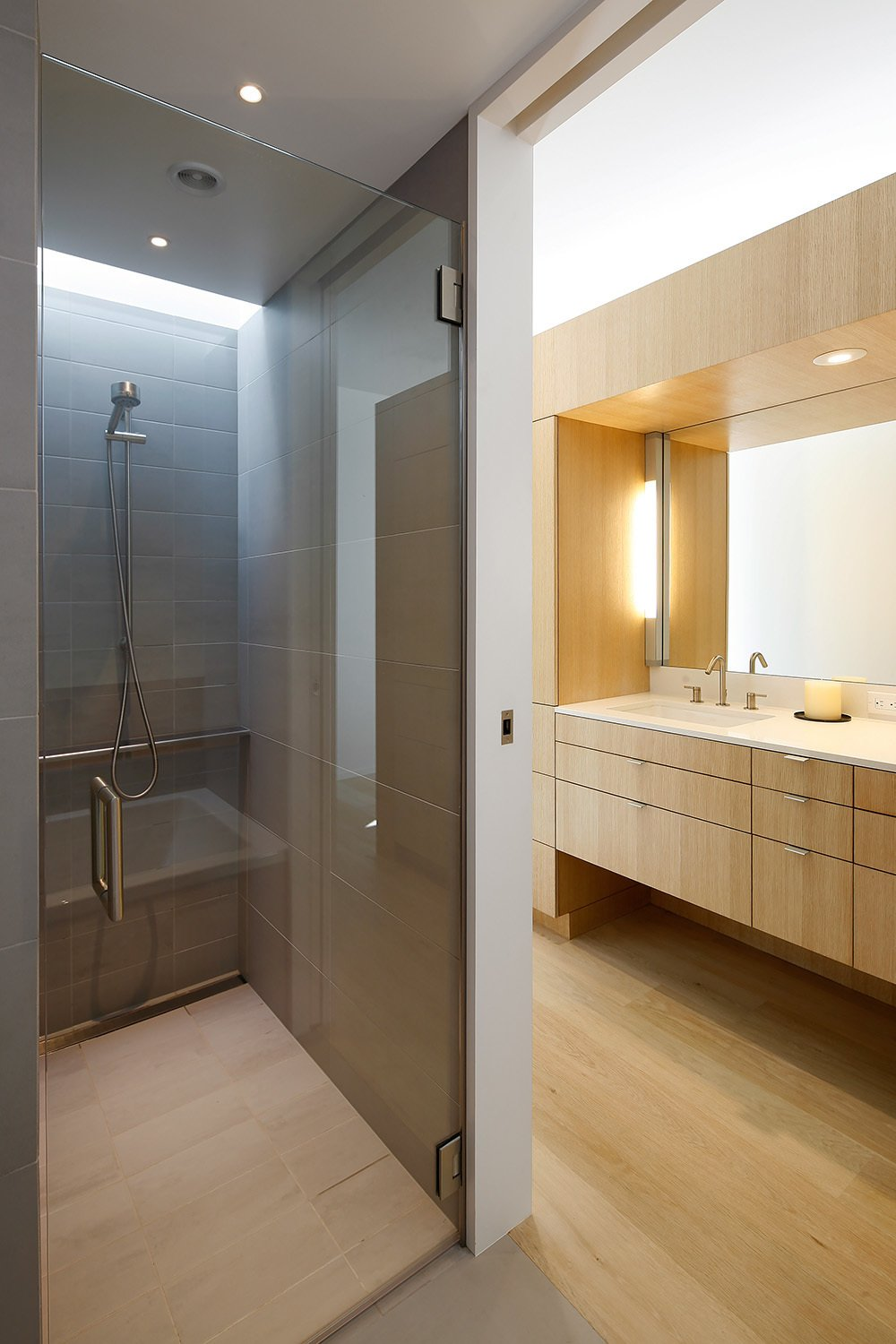 A Hansgrohe Raindance shower head is mounted behind the glass in the master bathroom. A Kohler Ladina undermount sink sits under the vanity mirror.  Portage Bay Bungalow by Kelly Dawson