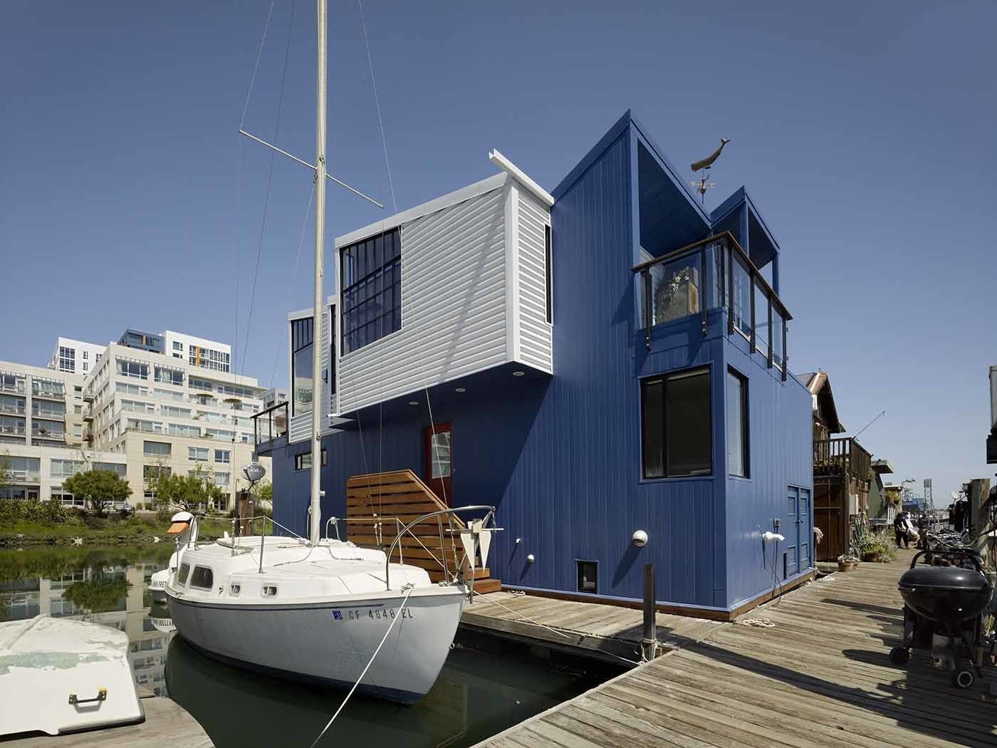 "Marked by its sawtooth roof and shipping container–like facade, the home is moored to the dock alongside boats. Since there's no way to paint a floating house, Nebolon chose to clad the exterior in 24-gauge metal siding coated with a fluorocarbon finish that will resist fading and chalking for 40 years. ""It's a very durable paint system that doesn't require periodic painting,"" he explains. ""An annual hose-down will work just fine.""  Photo 2 of 9 in Like a Loft on Water"
