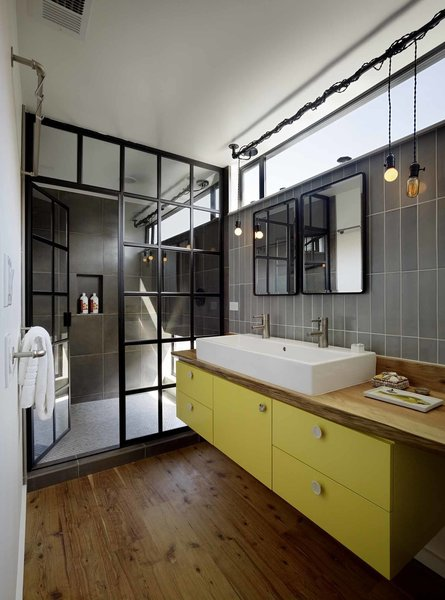 In the bathroom, a teak live-edge countertop and custom yellow cabinet support a double wash basin by Duravit. A mirror from Restoration Hardware hangs below custom lights, designed by the homeowner for a steampunk look.