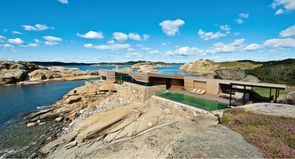 In Southern Norway, the Summer House by Jarmund/Vigsnæs AS Arkitekter MNAL is designed to blend in with its rocky site. Existing stone walls and a new wood exterior help achieve visual uniformity.