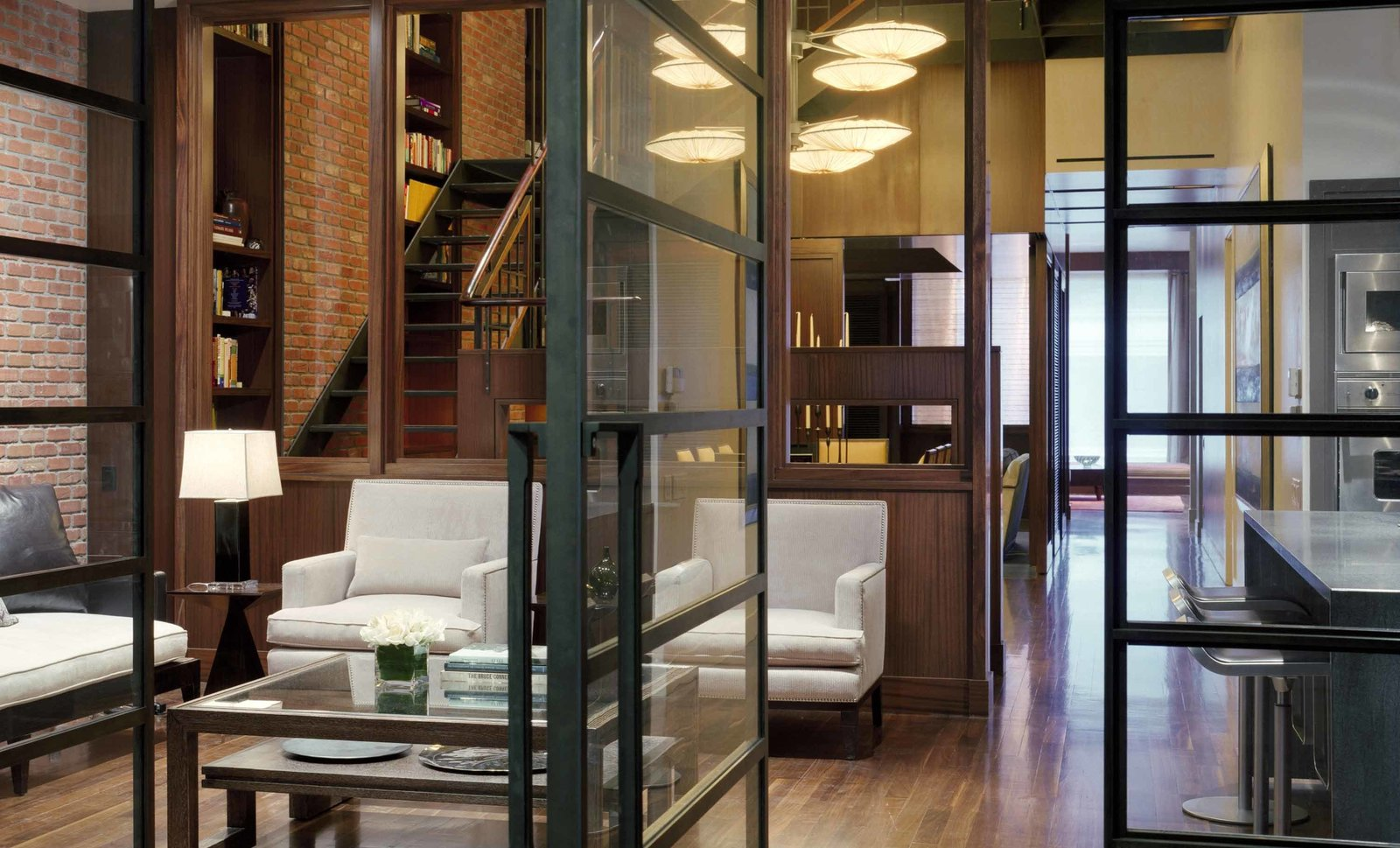 """SPAN balanced the owner's passion for Arts and Crafts architecture with an """"unabashedly urban"""" sensibility, encapsulated by the exposed brick wall. Impressed with the results, the client tasked the firm with designing his Maine hideaway along similar aesthetic lines. The kitchen banquet is custom by SPAN.  A Warm, Luxurious New York City Duplex with a Dramatic Catwalk by Luke Hopping"""