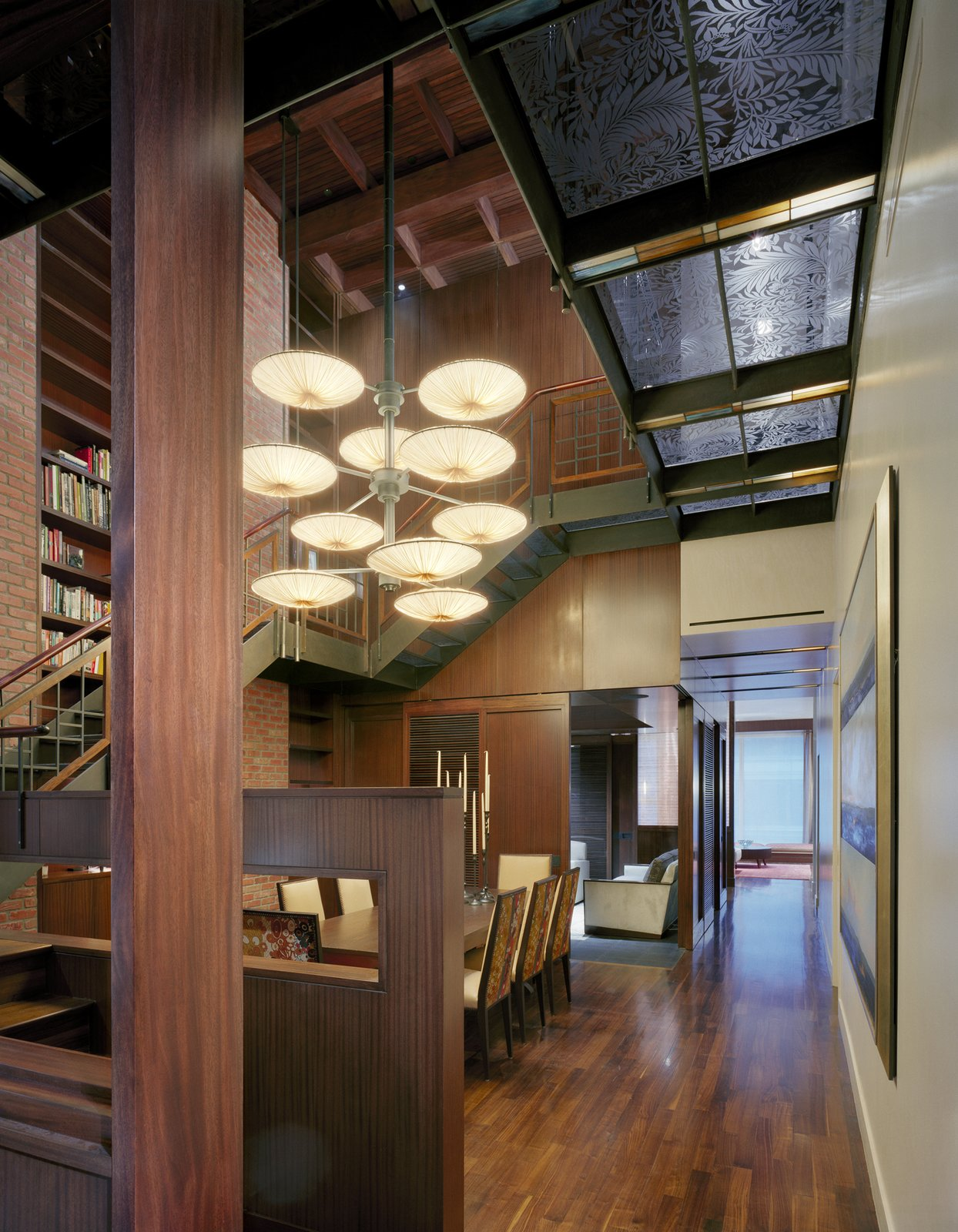 Dining Room, Accent Lighting, Ceiling Lighting, Medium Hardwood Floor, Table, and Chair SPAN Architecture recast this two-level space in New York City—previously a photography studio—as a loft-like residence that is rich in materials. A blackened steel staircase, executed by general contractor Richard Kaleta, leads to the private quarters on the duplex's second floor. The walkway is composed of custom etched glass, stretched across an open atrium to below.   Photo 8 of 18 in 18 Homes That Keep Things Fresh With Central Atriums from A Warm, Luxurious New York City Duplex with a Dramatic Catwalk