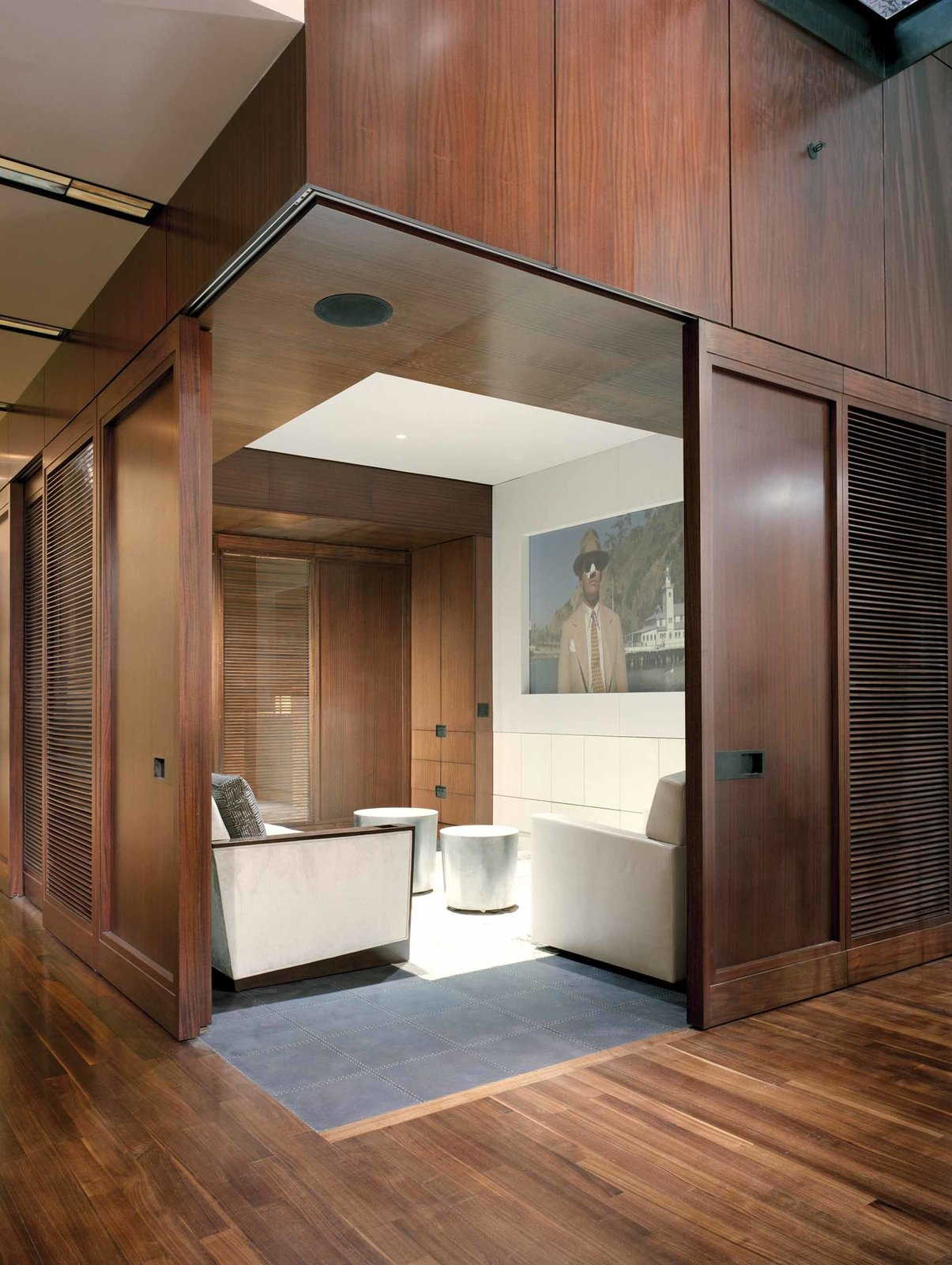Doors, Sliding Door Type, and Wood Sliding doors partition a cozy screening room, where the resident can enjoy films and television in the comfort of custom designed furniture.  A Warm, Luxurious New York City Duplex with a Dramatic Catwalk by Luke Hopping