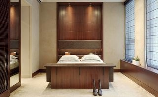 """Envisioned as """"an apartment within an apartment,"""" the master suite is secluded from the rest of the home, accessible via the steel-and-glass catwalk. The owner's sanctuary features a built-in bed and credenza by City."""