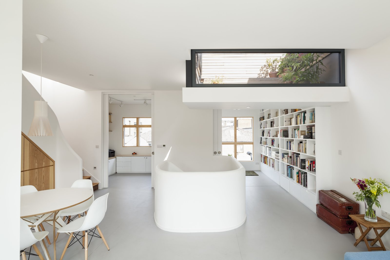 Stark white walls, off-white flooring, and bursts of wood grain energize the space.  Photo 2 of 7 in A Clever Sunken Roof Fills a London Terrace House with Light