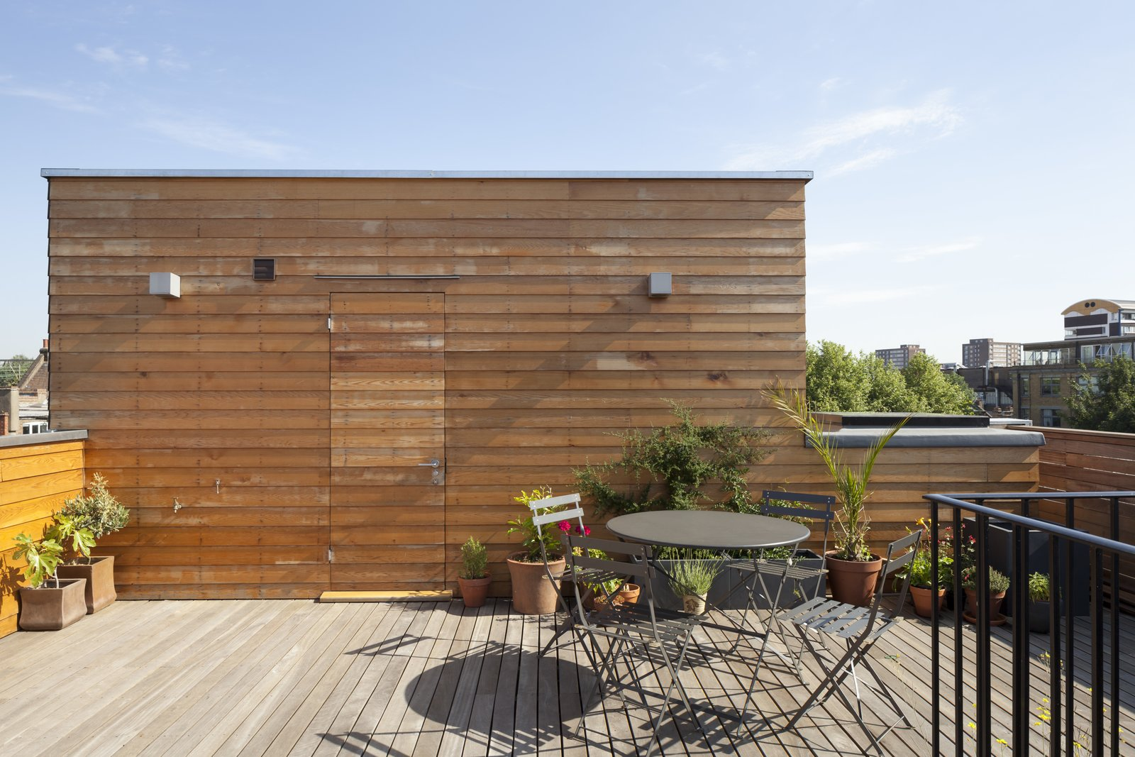 The private roof deck is clad entirely in wood planks and panels. Out of frame, the sunken garden made of structural laminate dunks into the living space below.  Photo 7 of 7 in A Clever Sunken Roof Fills a London Terrace House with Light