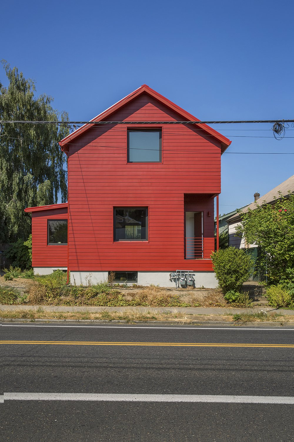 Two-foot-deep windowsills were carved out of the facade to augment the home's sculptural profile.  A Bright Red Farmhouse-Style Home That's Surprisingly Modern Inside by Luke Hopping