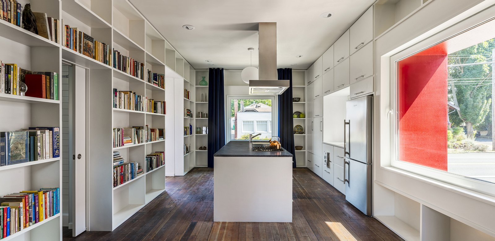 Inside, neutral tones and clean, modern lines prevail. Waechter designed each floor around a primary room, like the open-plan kitchen, with supporting spaces spread out around it.  A Bright Red Farmhouse-Style Home That's Surprisingly Modern Inside by Luke Hopping