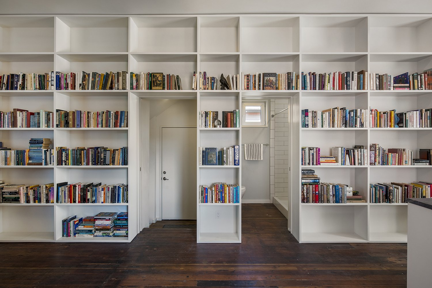 A wall of built-in shelving runs the length of the space, providing ample room for the residents' book collection.  Photo 8 of 11 in 10 Ways to Solve Storage Problems in Small Spaces from A Bright Red Farmhouse-Style Home That's Surprisingly Modern Inside