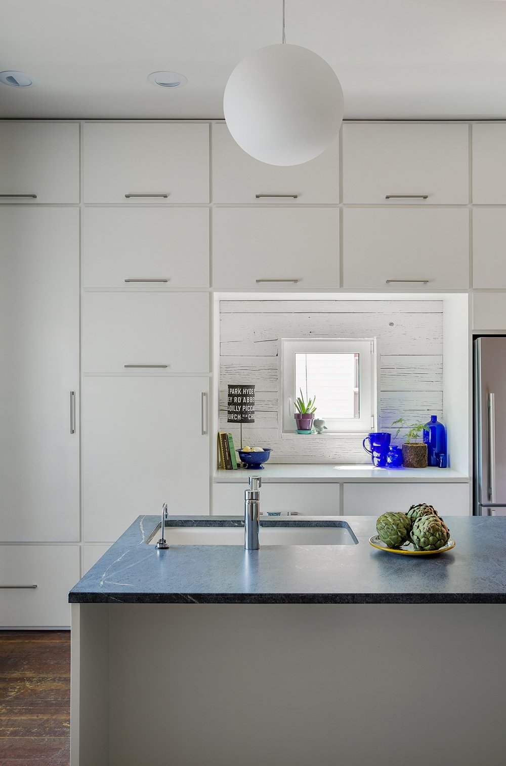 In addition to shelving for books, the architects dedicated plenty of space to storing groceries, kitchenware, and practical items.  A Bright Red Farmhouse-Style Home That's Surprisingly Modern Inside by Luke Hopping