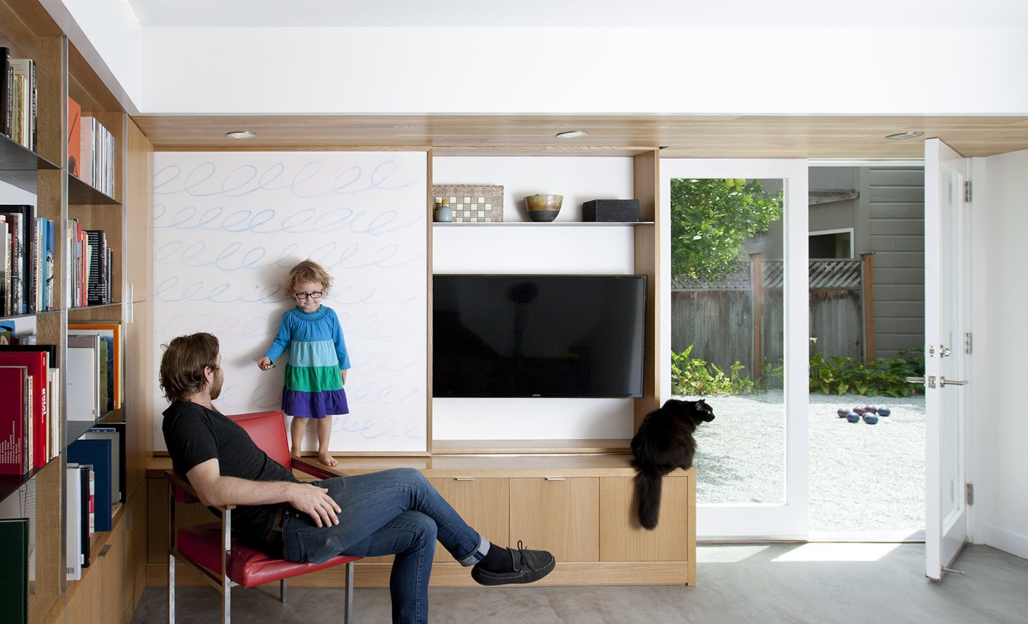 "The sliding wall panel is seen in its open position. In addition to several design elements serving multiple functions, great care was taken to develop a compelling design within the constraints of existing conditions. The remodel was confined to the existing building envelope, leaving the original footprint unchanged, but adding about 650 square feet of habitable space in the process. ""The plans,"" explains Paré-Mayer, ""respected existing structural conditions where possible to save on cost."" The finished concrete floor is, in fact, the structural slab, an efficient choice from a cost and materials perspective. The existing footings, which were wider than the framed interior walls, were kept intact in their original condition and location. The team was able to cleverly design around them by building usable closed storage to conceal the protruding foundation, as seen at the base of the media built-in.  KS Mission by Sarah Akkoush"