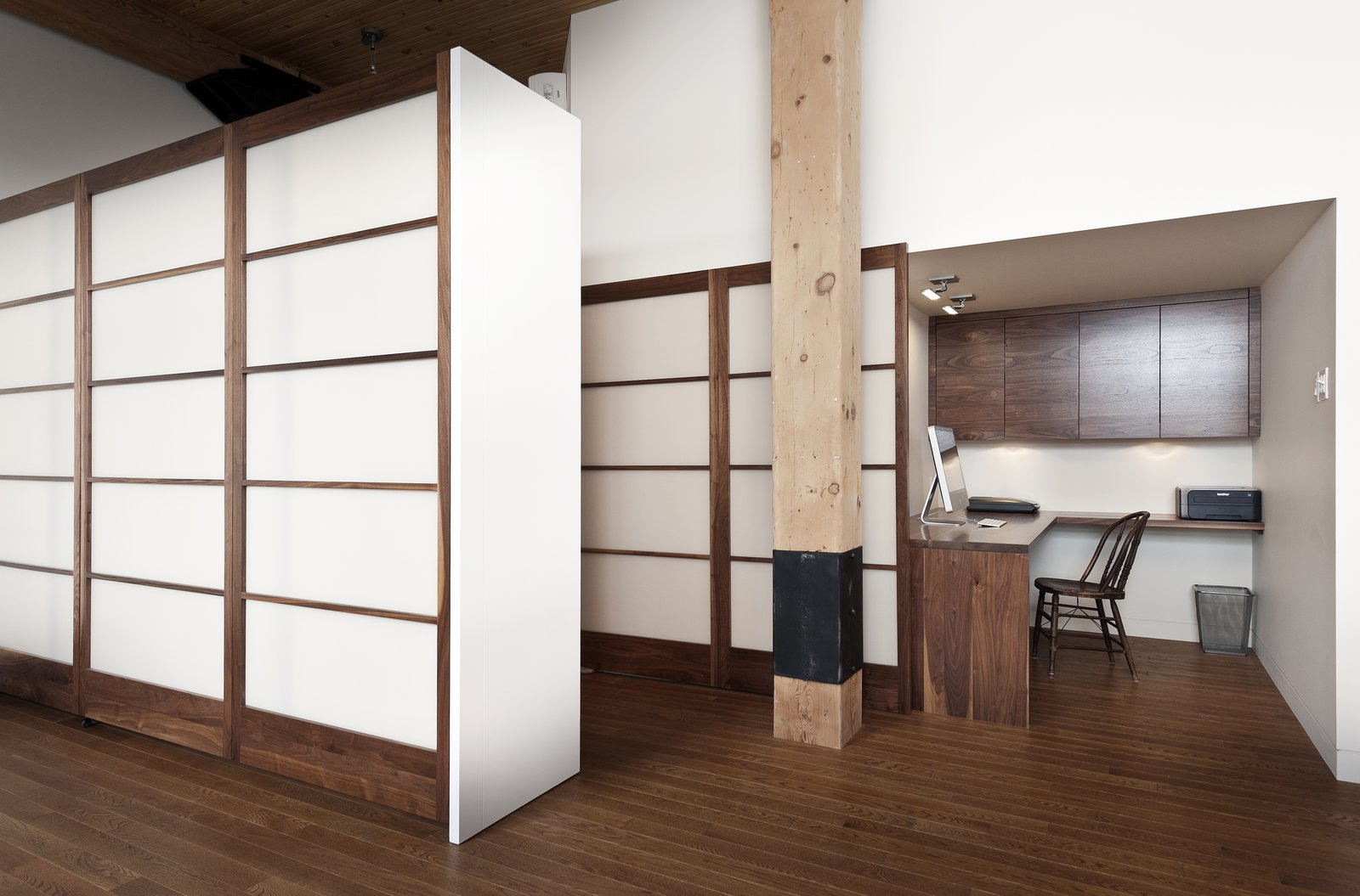 While the homeowners were inspired by shōji screens, the challenge was how to secure them. Gepetto's solution was a sliding three-panel screen anchored at one end of the wall unit.  Brick House by Caroline Wallis