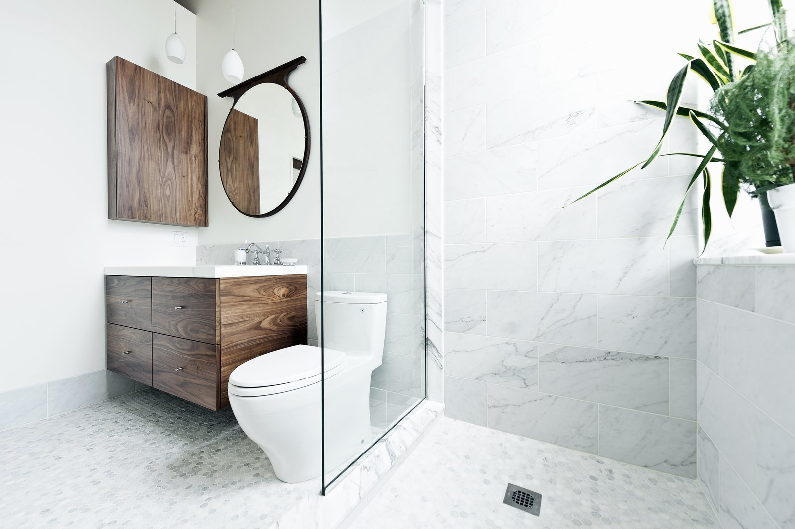 """Bath, Porcelain Tile, Pendant, Open, Engineered Quartz, Two Piece, and Marble """"What could I have that would feel luxurious, would make me feel really great?"""" muses one of the homeowners. """"My husband and I travel a lot in Europe, and we always loved the marble showers. So we put a marble shower up against the window."""" The sink and countertop are from Batimat, while the wall-hung vanity is another custom piece by Gepetto.  Best Bath Marble Pendant Photos from Brick House"""