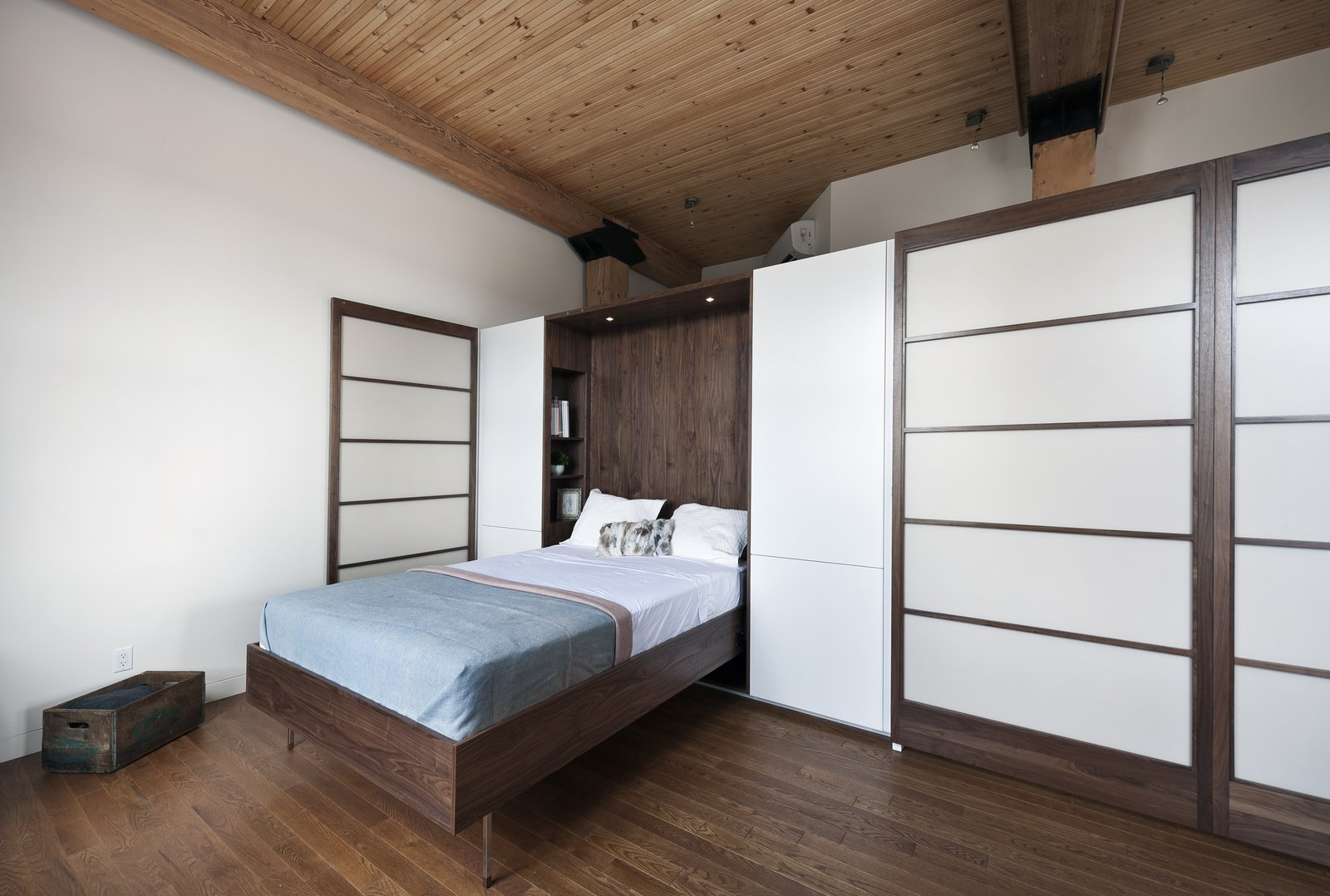 Gepetto built a Murphy bed that folds into a larger walnut storage unit. The wall, which also conceals a washer and dryer, does double duty as a partition between the bedroom and the loft's entrance. Tagged: Bedroom, Bed, and Dark Hardwood Floor.  Brick House by Caroline Wallis