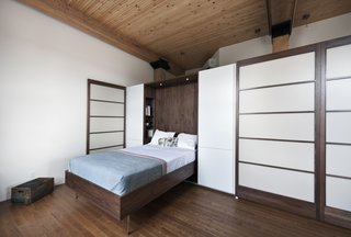 In an 850-square-foot loft in Montreal, Quebec–based firm Gepetto built understated, custom cabinetry to suit an aging couple's needs. Here, the Murphy bed that folds into a larger walnut storage unit. The wall, which also conceals a washer and dryer, does double duty as a partition between the bedroom and the loft's entrance. Modern Murphy beds like this one often incorporate sleek lines constructed in dark-toned woods.