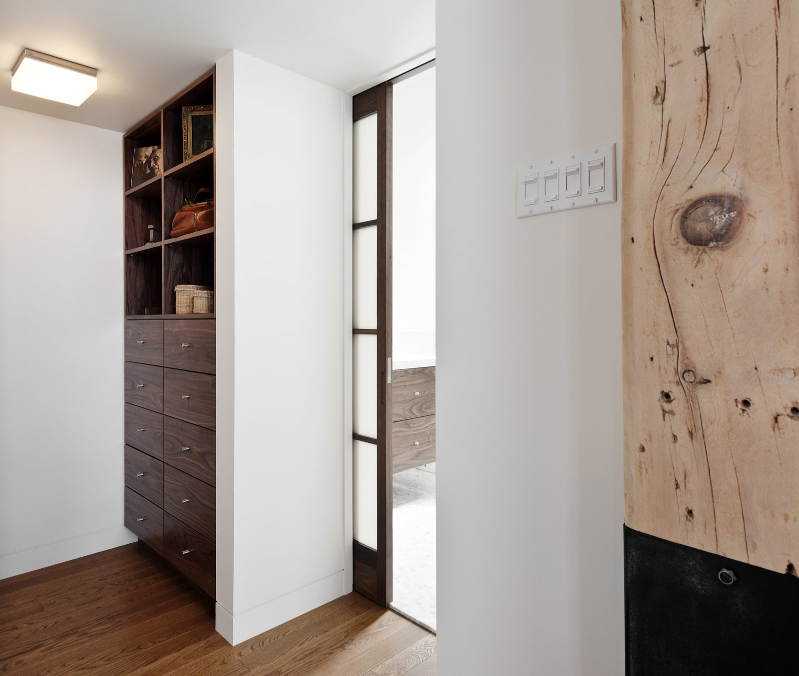 """The architects had to master the art of hiding storage throughout the apartment, including with this custom walnut organizer. As the homeowners near retirement age, the architects explain that the flat is a """"highly functional and sophisticated space that will serve them well as they begin another phase in their life together.""""  Brick House by Caroline Wallis"""