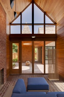 A Douglas fir ceiling in the screened porch and red bricks are accented by blue Arizona modular outdoor seating by Barlow Tyrie.