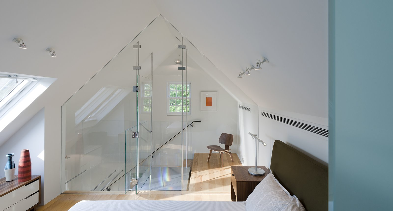 Bedroom, Wall Lighting, Bed, Chair, Night Stands, and Table Lighting Aside from the master bedroom, there are three additional bedrooms in the house. Gurney and his team used glass throughout to carry light into the home. A Copenhagen nightstand supports a Brazo table lamp in this third-floor guest room.  Best Photos