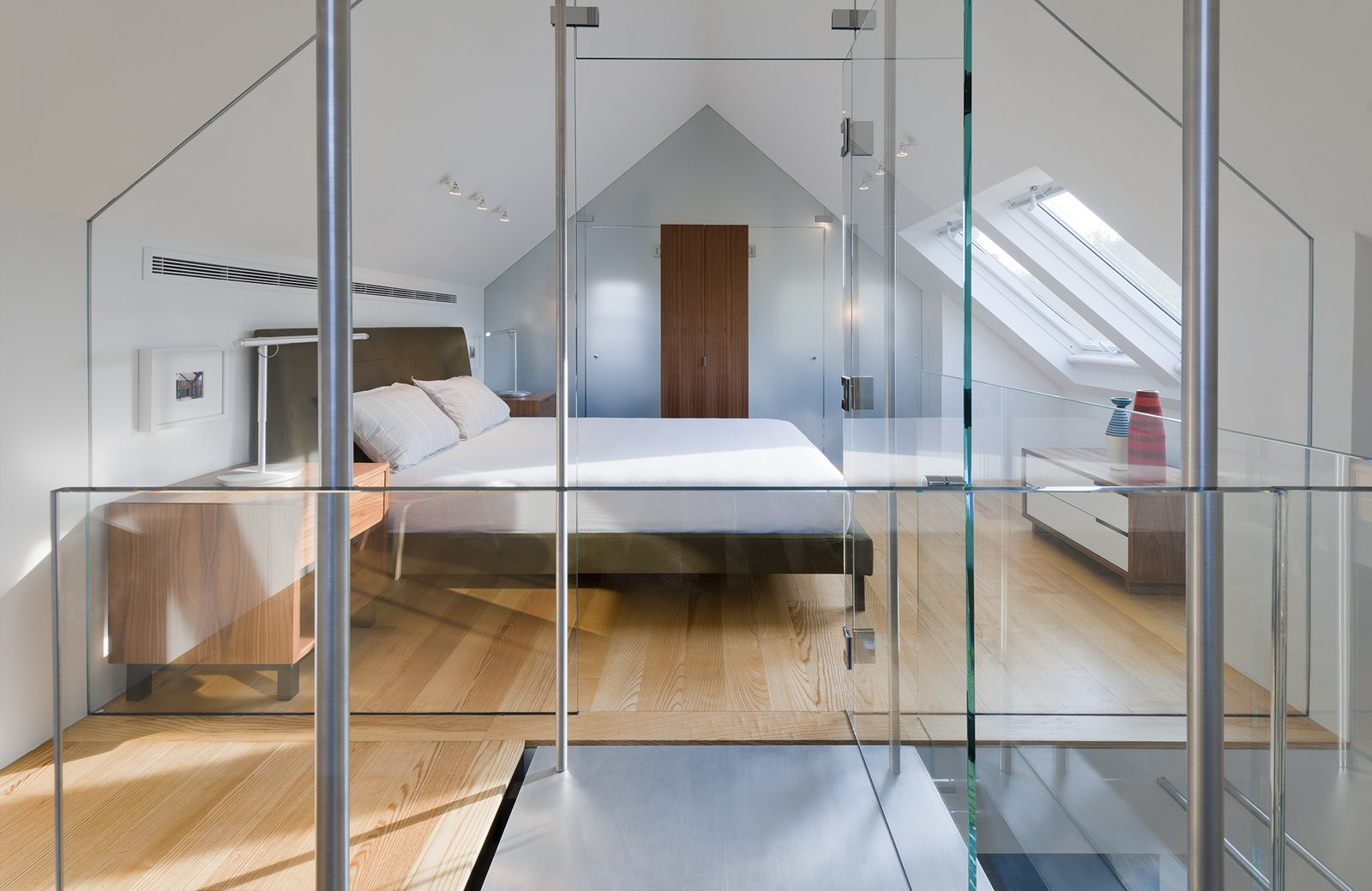 """This custom glass structure by Ilex Construction allows for an abundance of light during the day. At night, Lightolier fixtures on the ceiling illuminate the Ella bed. Sherwin-Williams """"Pure White"""" was painted on all interior walls.  Bedrooms by Dwell from A Traditional Facade Hides A Light-Filled Modern Delaware Renovation"""