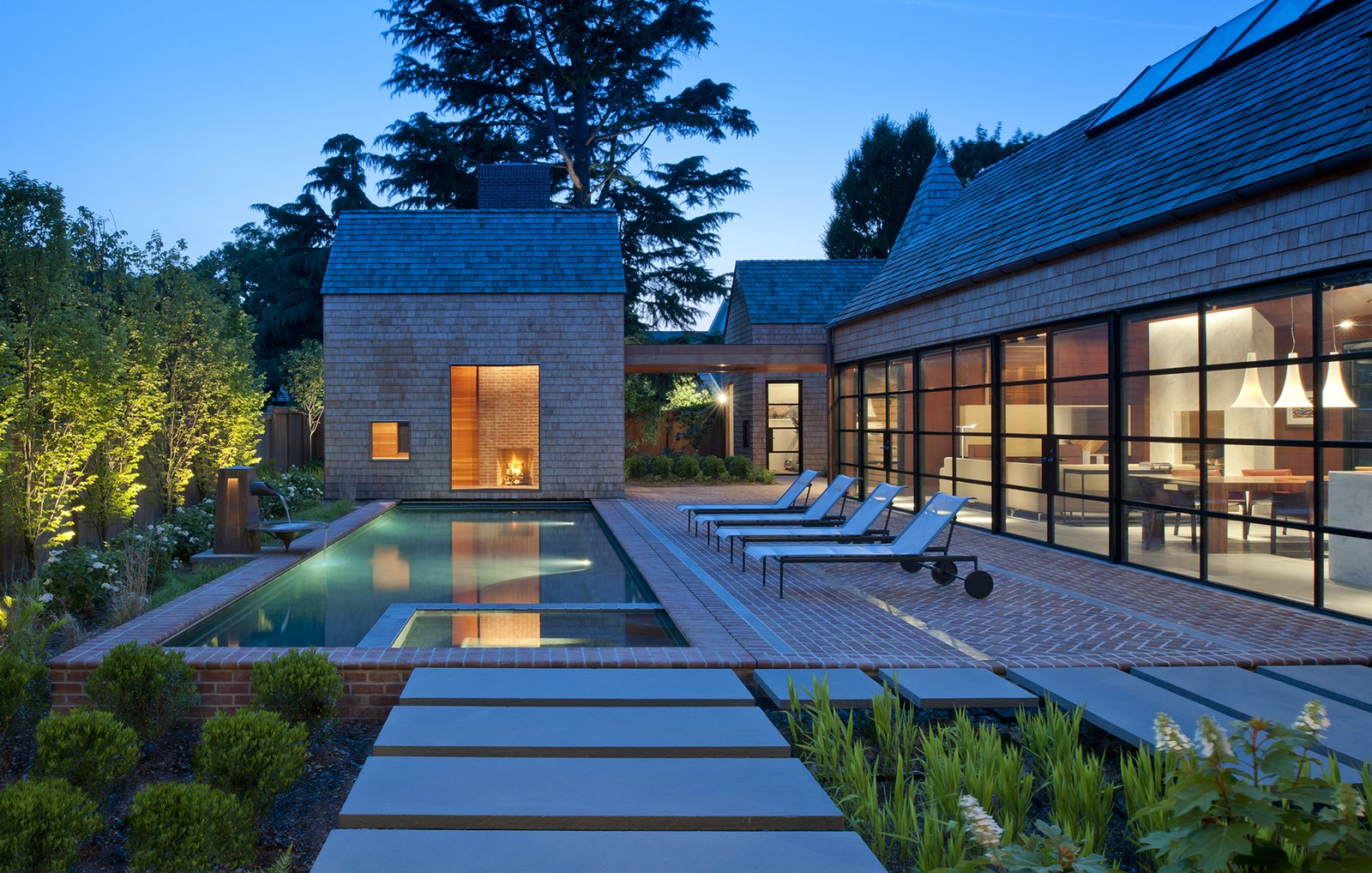 Outdoor, Large Patio, Porch, Deck, Landscape Lighting, Walkways, Large Pools, Tubs, Shower, and Trees Outdoor lounge chairs by Richard Schultz sit on brick floors. The pool's changing pavilion features a full bathroom.  Photo 10 of 10 in A Traditional Facade Hides a Light-Filled Renovation in Delaware from Breathtaking Tones of Blue