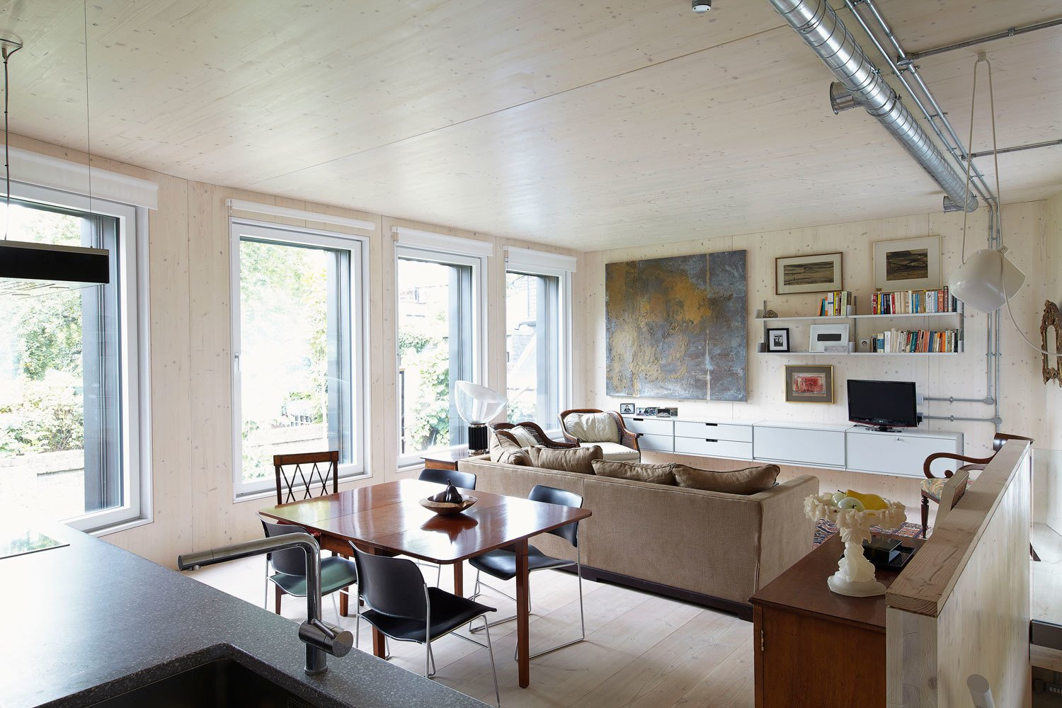 The approximately 1076-square-foot, two-bedroom dwelling was built by architect Bernard Tulkens for his parents-in-law. It is the fifth certified Passive House to be completed in London. Natural Douglas fir flooring by Dinesen covers the living area, which contains shelving by Vitsoe.  15+ Passive Modern Home Ideas by Heather Corcoran from Small But Mighty Passive House in London
