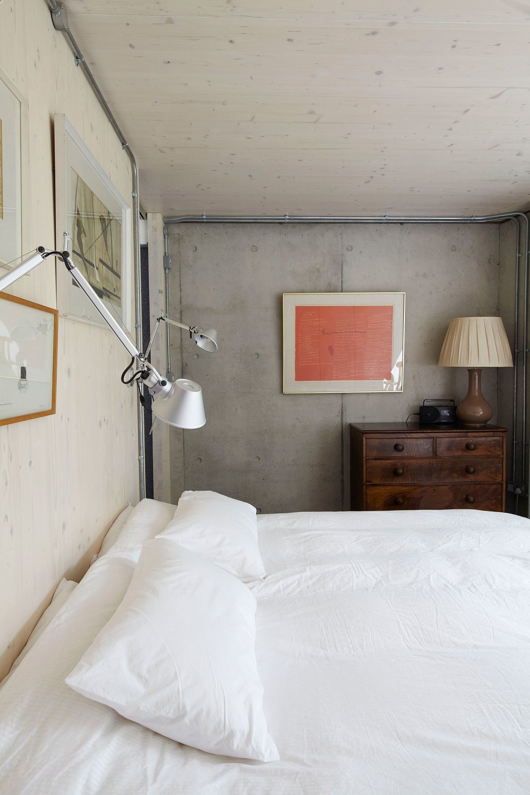 The lower level has a reinforced concrete frame. The timber and concrete surfaces are left exposed throughout the home. Tolomeo lights from Artemide hang above one of the beds.  Concrete from Small But Mighty Passive House in London