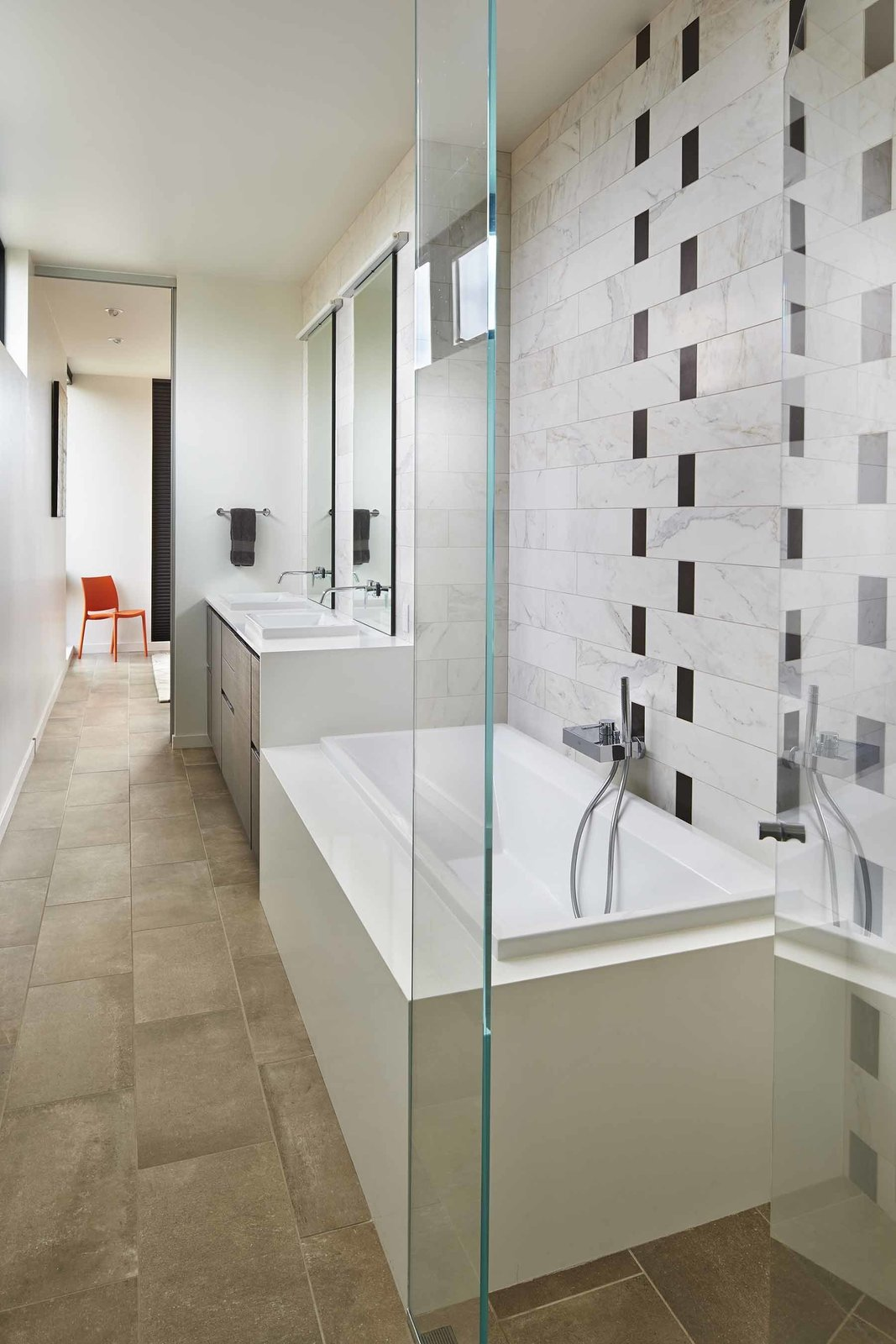 In the master bathroom, a Duravit tub and pair of sinks are surrounded by black and white Crossville tile.  A Light-Filled Renovation Helps a 1950s Seattle Home Go Green by Tiffany Jow