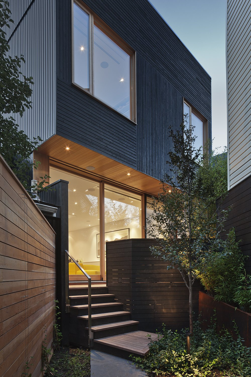 """""""The black siding is contemporary, but the texture of the wood grain is friendly and complements more traditional neighboring houses,"""" Clarkson said. Windows are fabricated with Douglas fir. Ipe and stained black cedar make up the home's various decks.  King West by Kelly Dawson"""