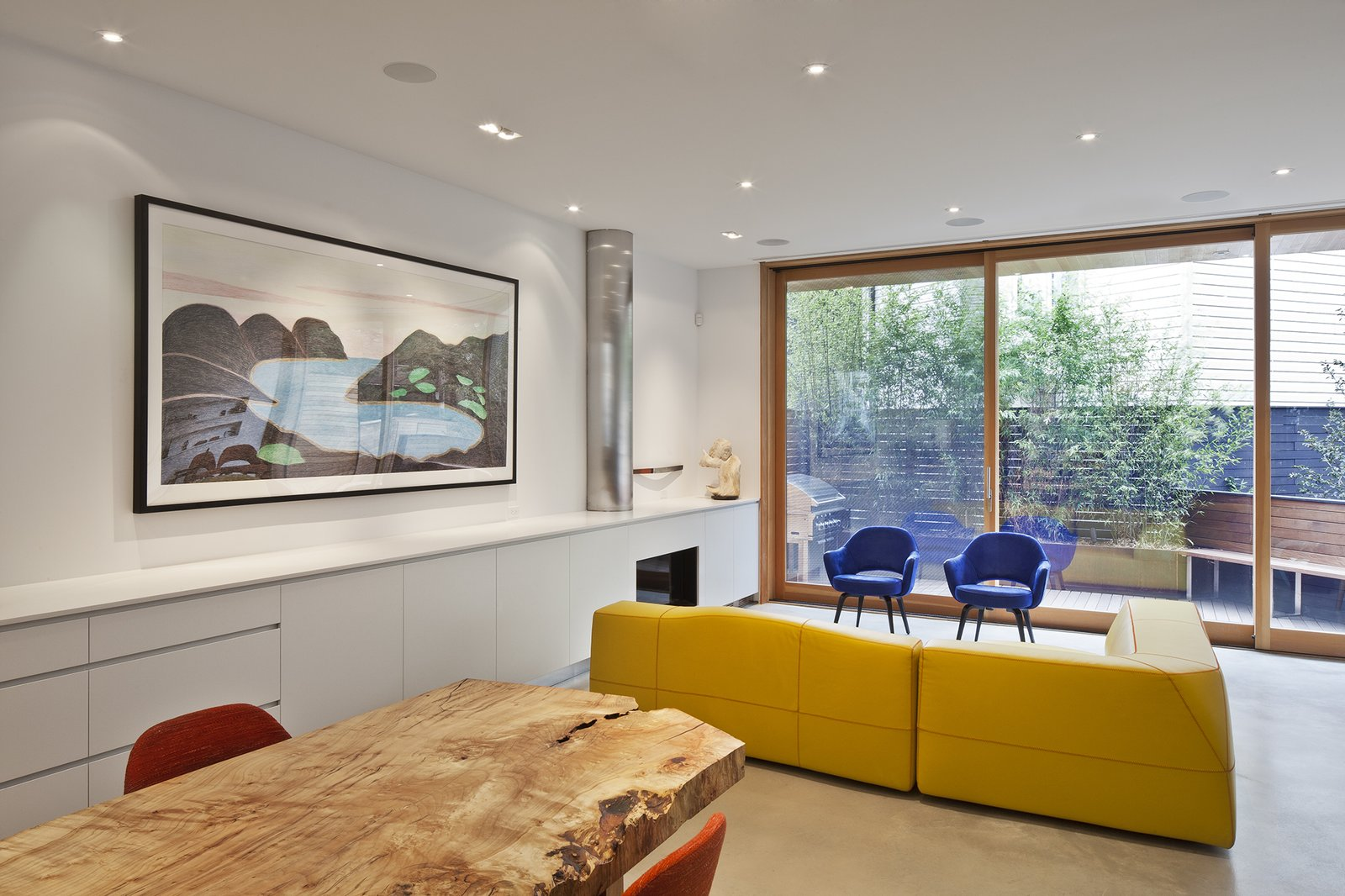 """""""The [design] is simple and flexible, with an open plan on the first floor that allows the kitchen to flow into the dining and living spaces,"""" Clarkson said. Concrete floors help to unify the spaces, which feature a B&B Italia Bend-Sofa and Saarinen executive armchairs in royal blue velvet.  King West by Kelly Dawson"""
