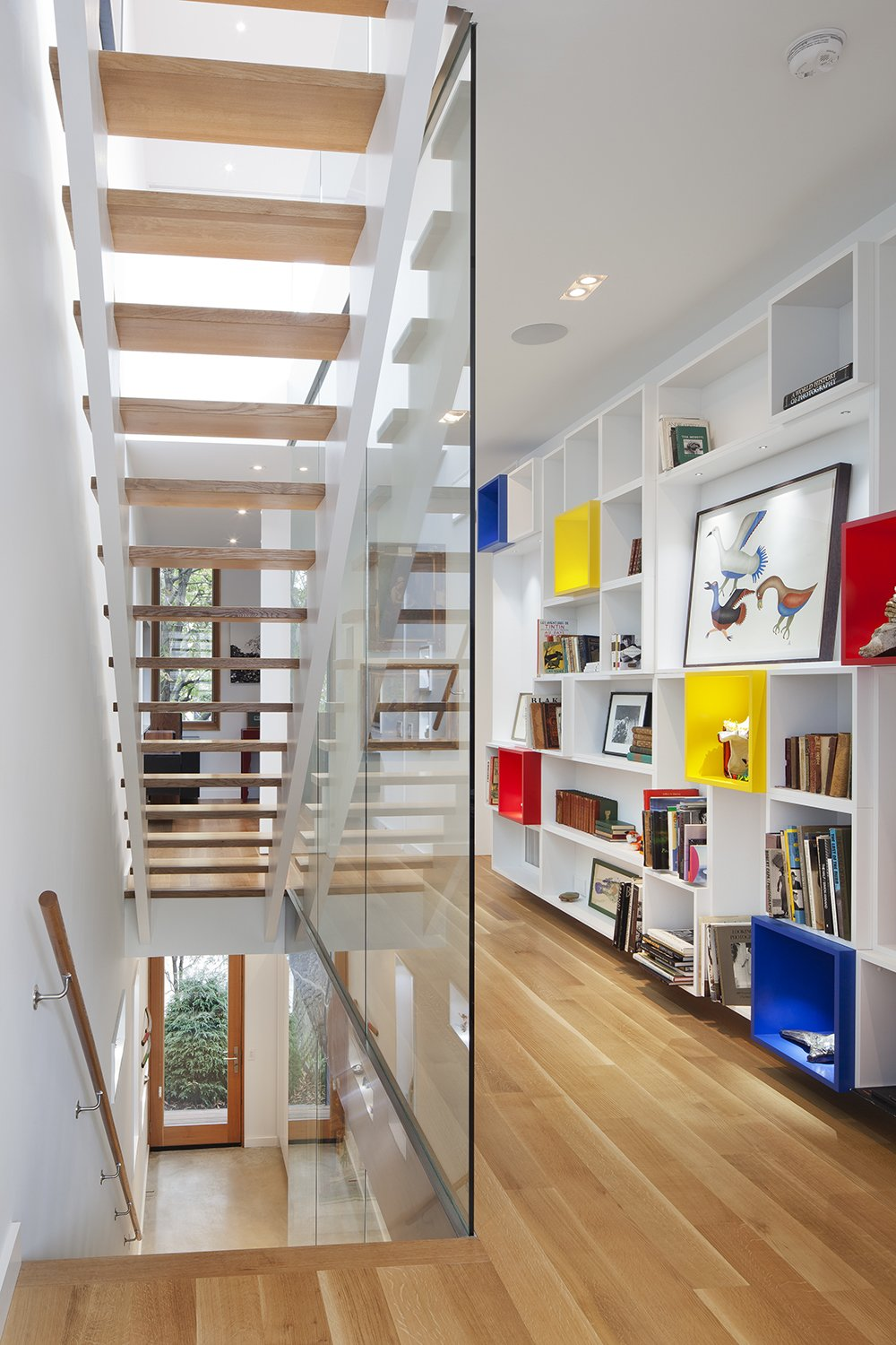"""""""The interior was designed as a backdrop to the art and life of its inhabitants,"""" Clarkson noted. """"A custom-built wall of display cubes adds an accent of primary color in the second floor hallway."""" Solid white oak flooring continues onto the second level from the stairs, and Middlebrook Woodworking Ltd. lacquered that same material for the display cubes.  King West by Kelly Dawson"""