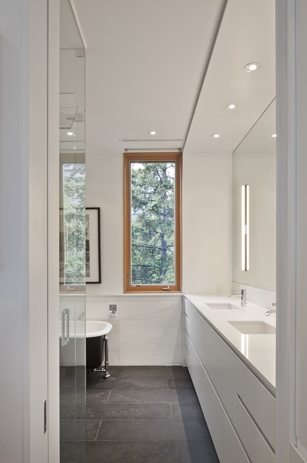 In the master bathroom, Dolomite marble was installed on the walls to complement Caesarstone countertops. Both contrast with the dark Montauk slate on the floor.  King West by Kelly Dawson