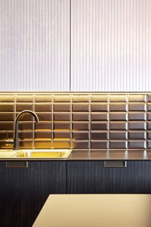 Golden brown subway tiles from Diffusion Ceramique face a black countertop from Fundermax.