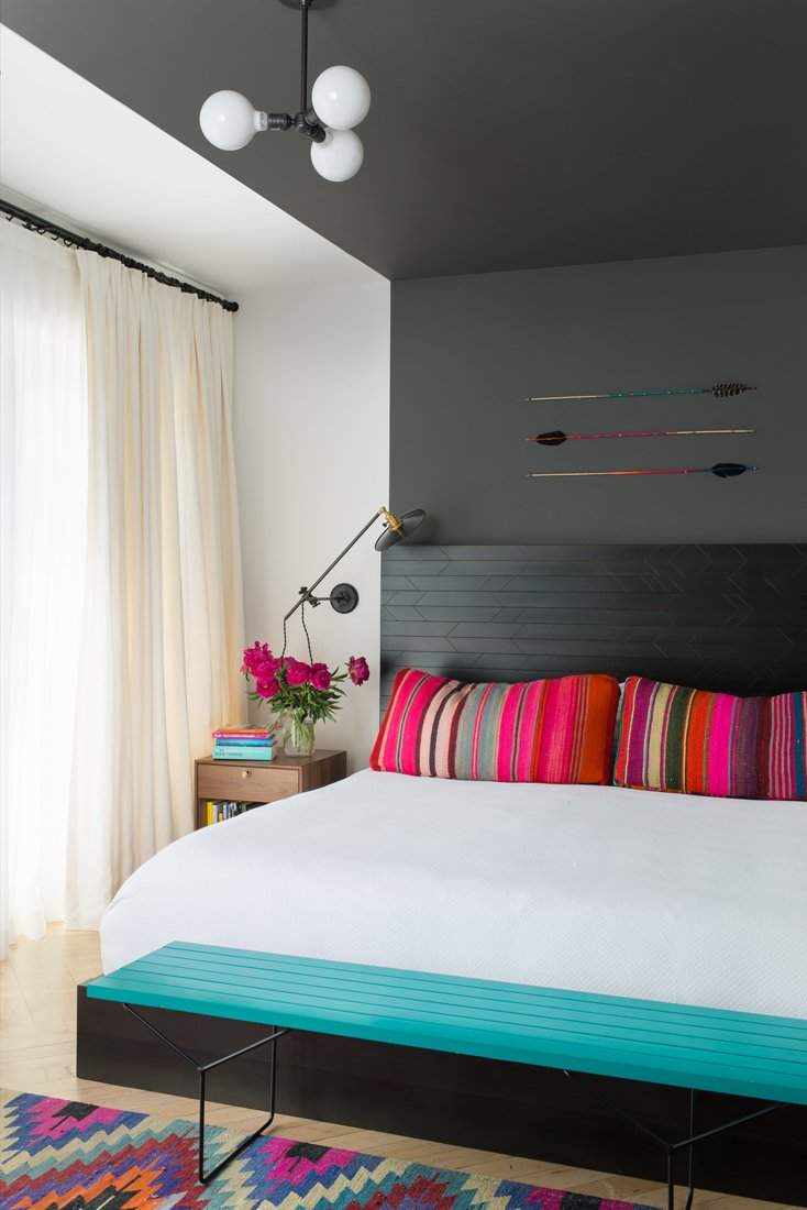 The bed in the master bedroom is a custom JHID design in ebony-stained fir. Lighting is kept subtle, in the form of an overhead fixture by Schoolhouse Electric and wall sconces by Workstead. The arrows are by Fredericks and Mae.  Color Splash by Kelsey Keith