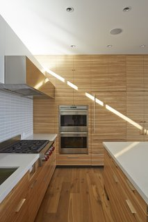Sleek Wolf and Sub-Zero appliances, along with Caesarstone countertops, complete the kitchen.