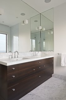 The clean symmetry of the master bathroom is enhanced by Ann Sacks ceramic Savoy tiles and Lefroy Brooks fixtures.