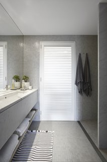 Carrara marble was used in the vanity and the bathroom partitions while shutters let in additional light from the outside.