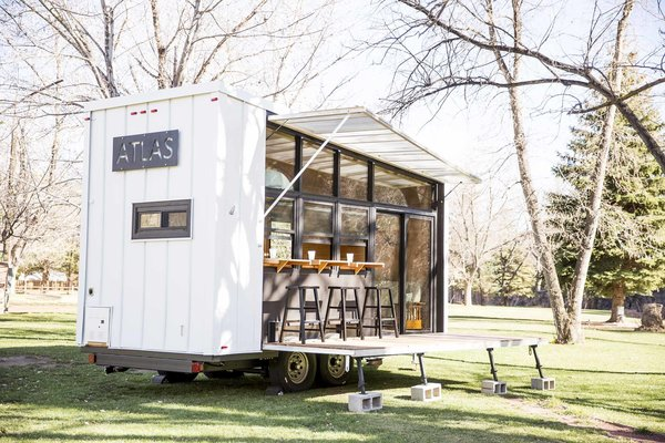 Unpacking the deck and awning reveals a glass wall that opens the trailer to its environment, wherever that may be. The ATLAS can be hitched to a truck to travel easily from campsite to campsite.