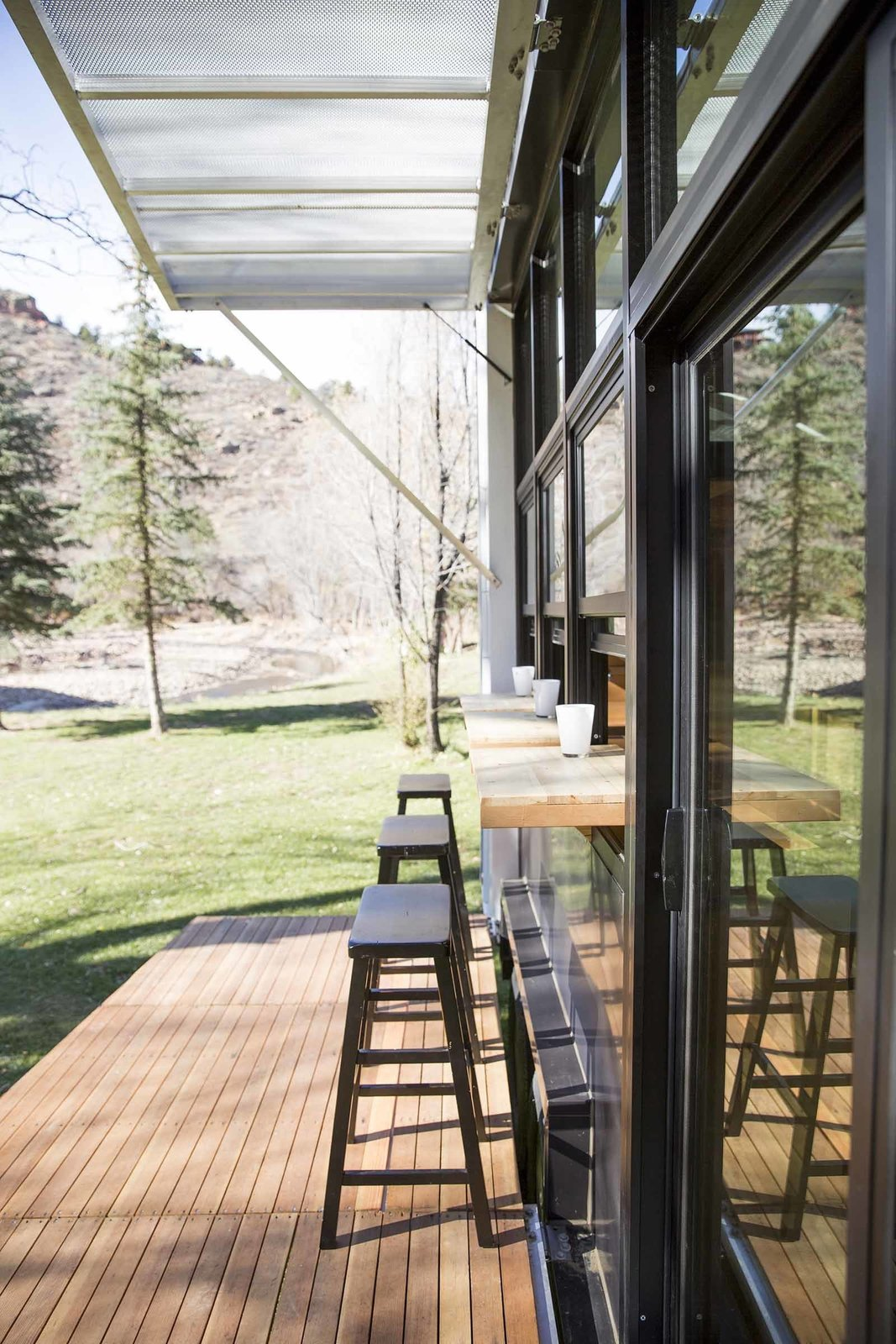 Generous windows and a split indoor-outdoor benchtop help bring the outside in.  A Tiny Trailer Home Harvests Solar Power and Rainwater to Save Energy by Luke Hopping