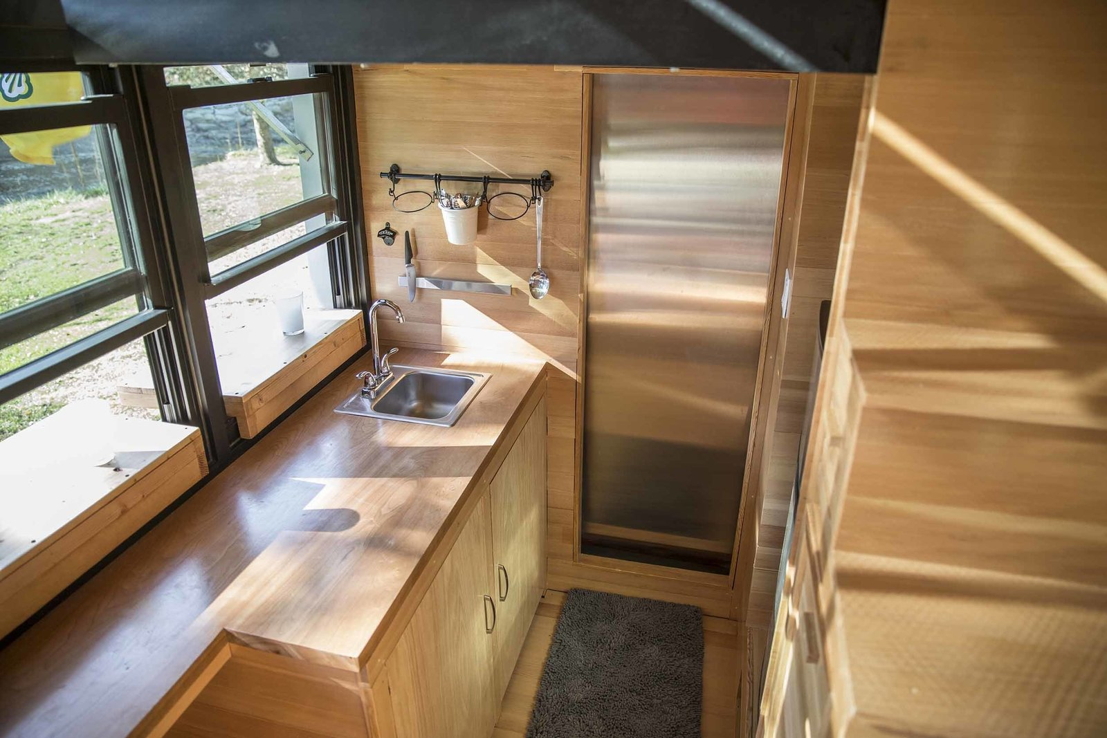 The all-wood interior features standard home appliances, such as a sink, induction cook top, and refrigerator.  A Tiny Trailer Home Harvests Solar Power and Rainwater to Save Energy by Luke Hopping