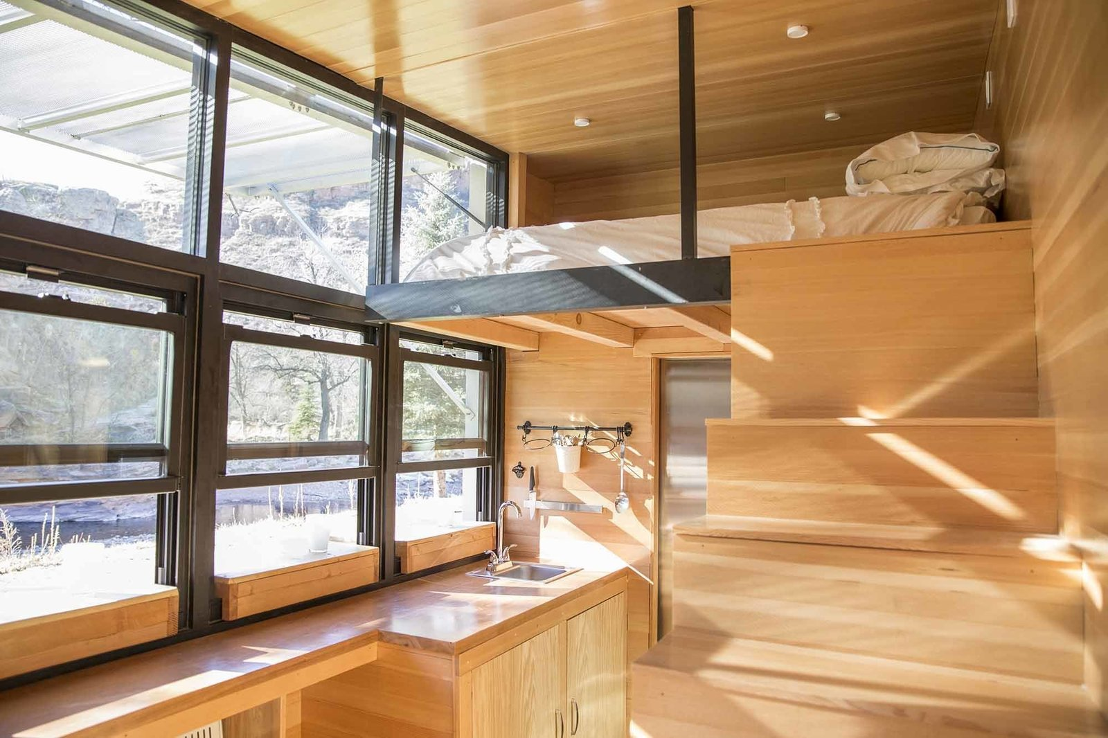 Kitchen, Wood Counter, and Wood Cabinet With a built-in sofa and sleeping loft, ATLAS can accommodate three adult travelers.  A Tiny Trailer Home Harvests Solar Power and Rainwater to Save Energy by Luke Hopping