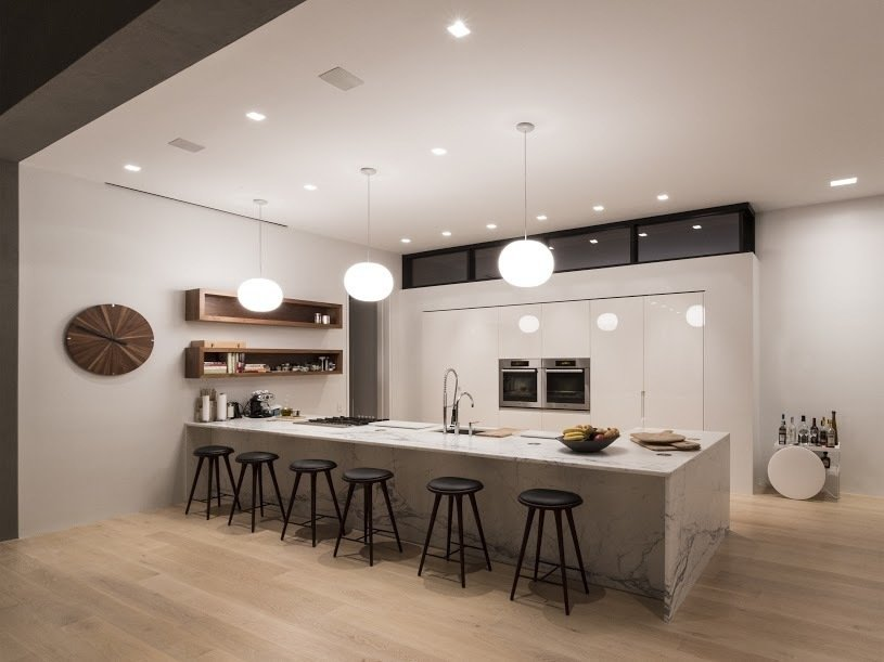 The minimalist kitchen features an array of lighting: can lights integrated into the ceiling as well as pendants.  Photo 4 of 6 in How to Integrate Smart Lighting into Your Home