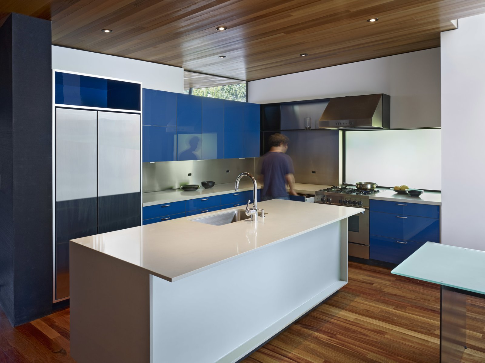 Kitchen, Colorful Cabinet, Medium Hardwood Floor, Metal Backsplashe, Engineered Quartz Counter, Ceiling Lighting, Range, Refrigerator, and Undermount Sink Accenting the warm wood tones, pops of cobalt blue are found throughout the home, including in the kitchen. The space, which anchors the new living wing, features custom lacquer finish cabinets, Caesarstone counters, a Bertazzoni range, a Miele dishwasher, a Kohler sink, and a custom stainless steel backsplash.  Photo 4 of 8 in An Indoor-Outdoor Renovation for a 1950s Ranch House in the Bay Area from 1950s Ranch