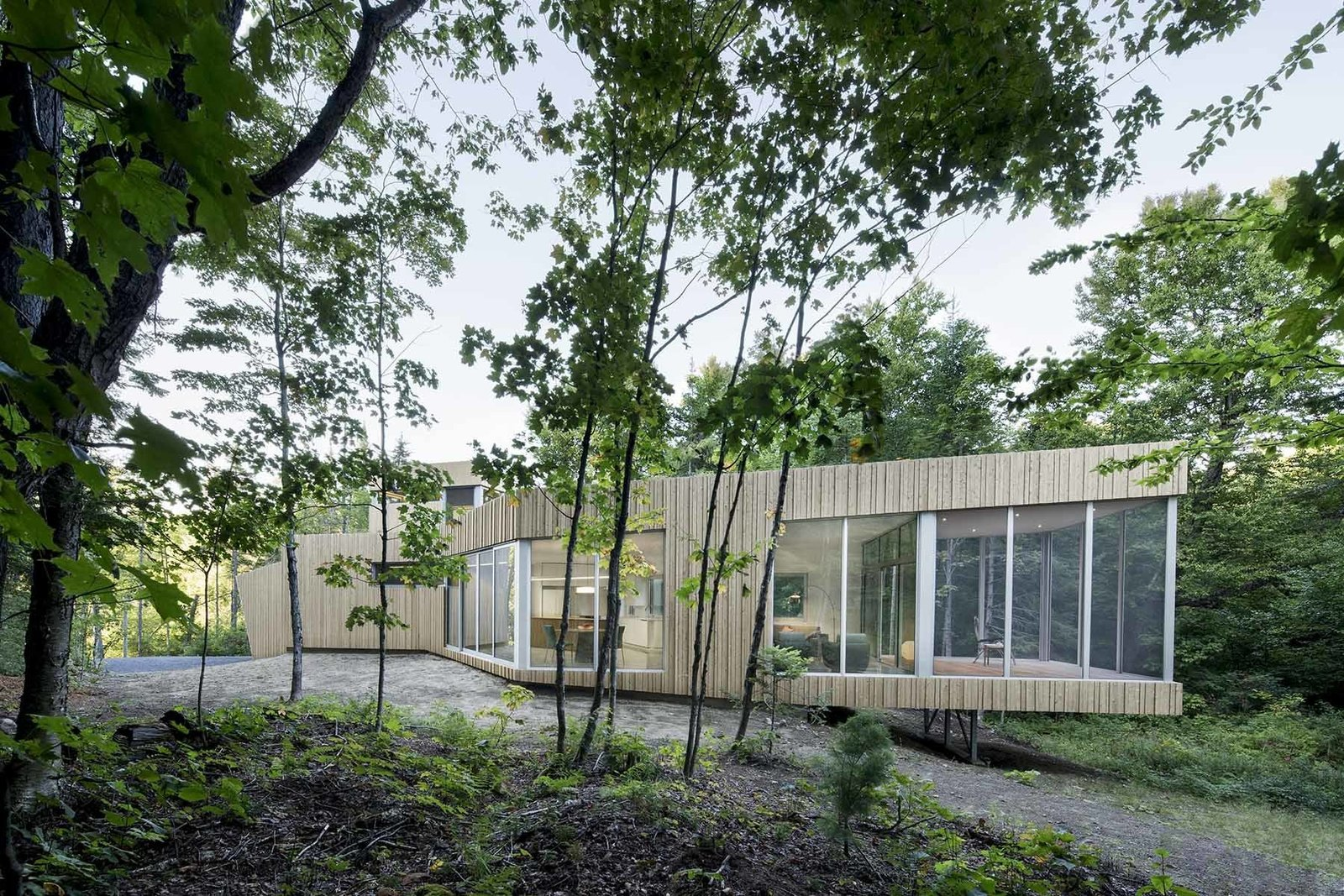 """Our central challenge was to add a home to the forest without undermining nature,"" architect Paul Bernier says. ""We allowed the house's function and relationship with its site to shape the design.""  Tiny Homes from House of Lake Grenier"